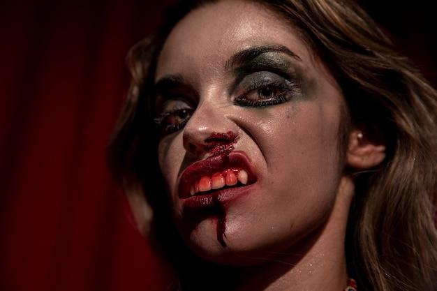 Vrouw met bloed bij haar gezicht het stellen