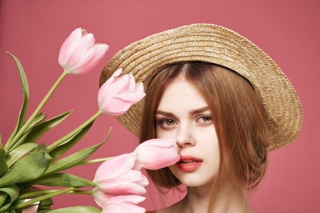 Vrouw met bloemen cadeau vrouwelijke vakantie mode roze achtergrond. hoge kwaliteit foto