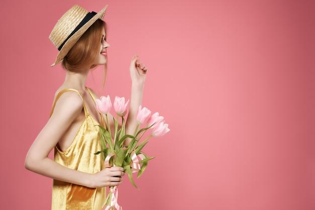 Vrouw met bloemen cadeau vrouwelijke vakantie mode roze achtergrond