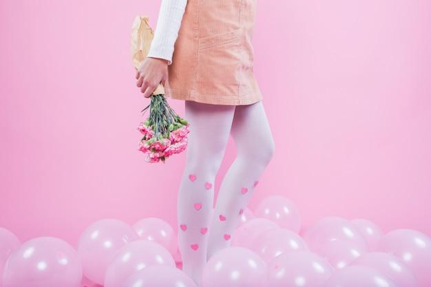 Vrouw met bloemen die zich op vloer met ballons bevinden