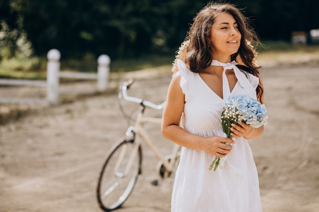 Vrouw met bloemen fietsten op het strand