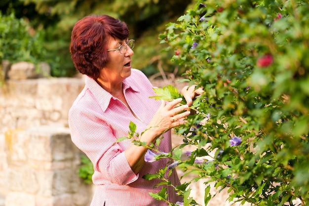 Vrouw met bloemen in haar tuin