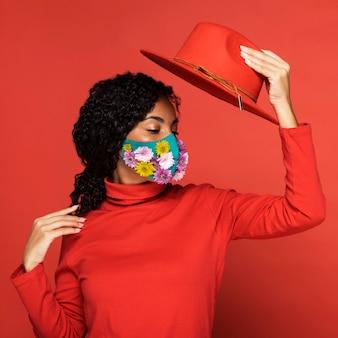 Vrouw met bloemen op haar masker poseren met hoed