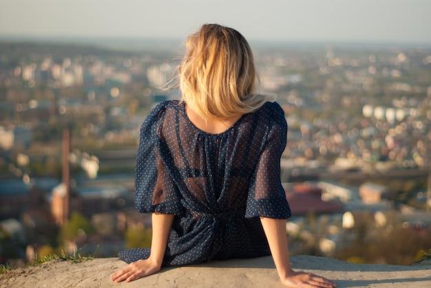 Vrouw met blond haar die van bovenaanzicht naar de stad kijkt