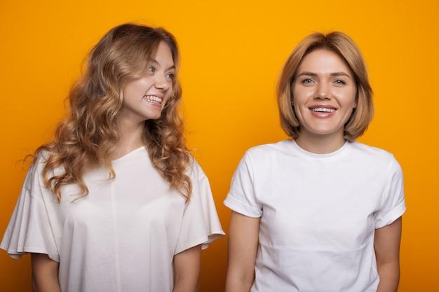 Vrouw met blond haar glimlach op haar zus kijken