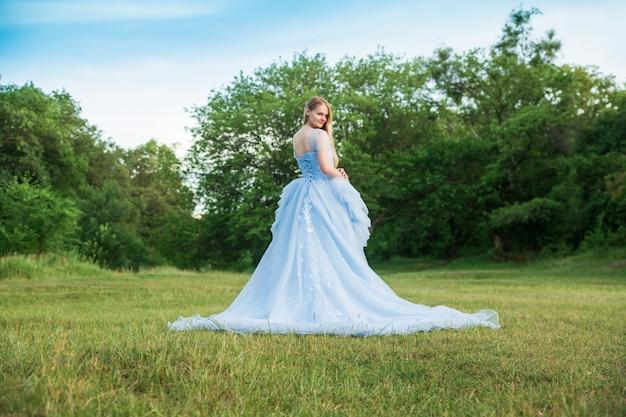 Vrouw met blond haar in een mooie blauwe jurk met lange mouwen buiten.
