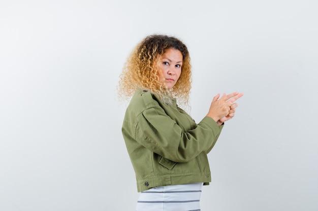 Vrouw met blond krullend haar in groen jasje wijst naar de voorkant van haar en kijkt aarzelend.