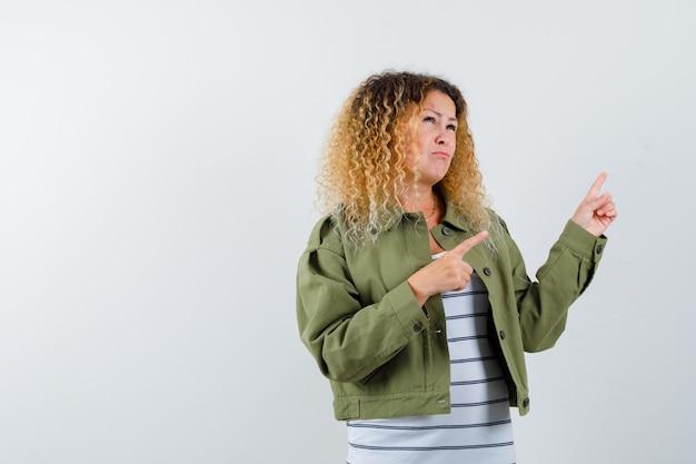 Vrouw met blond krullend haar in groen jasje wijzend op de rechterbovenhoek en peinzend, vooraanzicht op zoek.