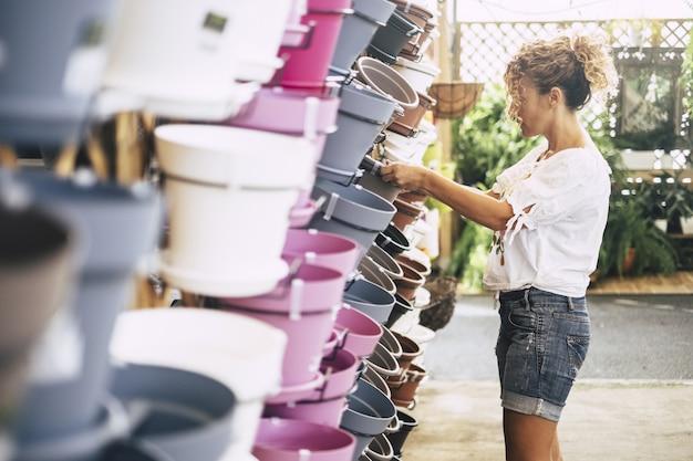 Vrouw met blond krullend haar kiest een vaas voor haar planten in de winkel.