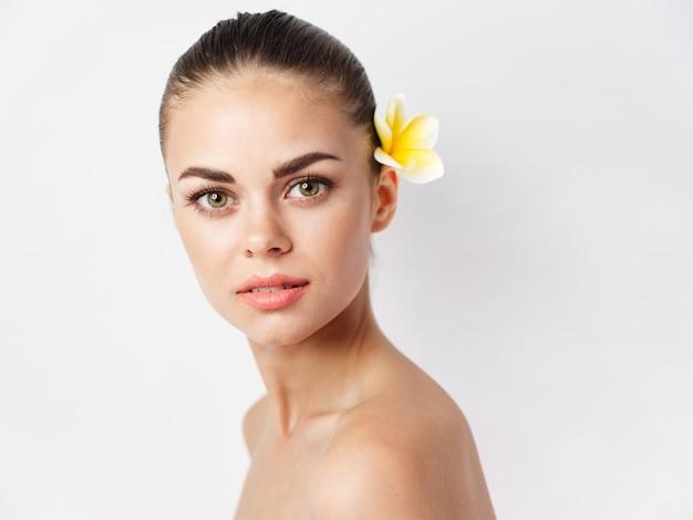 Vrouw met blote schouders aantrekkelijk uiterlijk gele bloem heldere huid lichte achtergrond