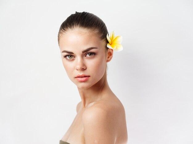 Vrouw met blote schouders aantrekkelijk uiterlijk gele bloem in haar charme lichte achtergrond