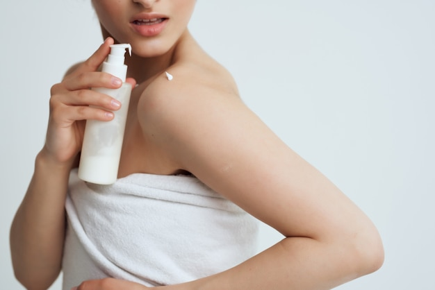 Vrouw met blote schouders die lotion aanbrengt op de huid hydraterende close-up