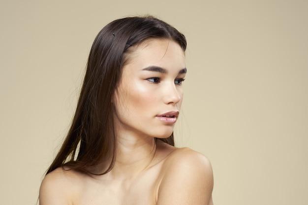 Vrouw met blote schouders donker haar schone huid make-up beige.