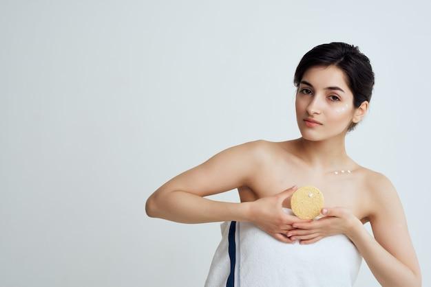 Vrouw met blote schouders en een spons in haar handen scrub schone huidverzorging