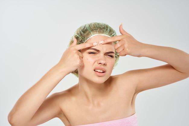 Vrouw met blote schouders knijpt acne op haar gezicht huidverzorging
