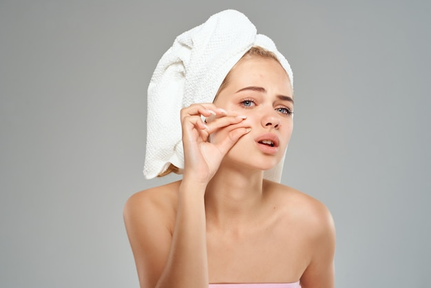 Vrouw met blote schouders knijpt puistjes op haar gezicht handdoek op haar hoofd lichte achtergrond
