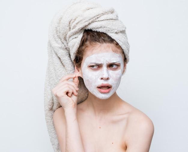 Vrouw met blote schouders met een handdoek op haar hoofd het gezichtsmasker van de huidzorg