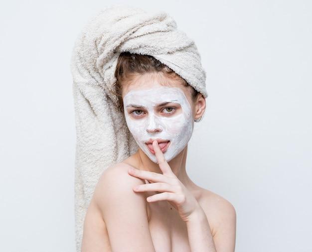 Vrouw met blote schouders met een handdoek op haar hoofd huidverzorging gezichtsmasker.