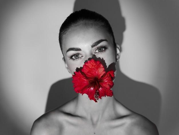 Vrouw met blote schouders met een rode bloem in haar mond zwart-wit foto