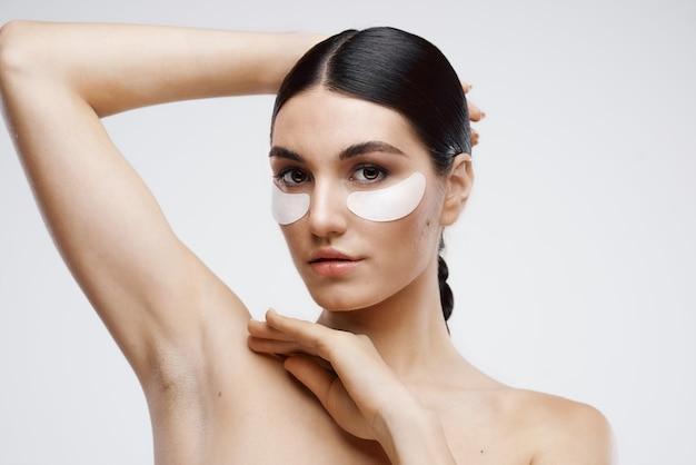 Vrouw met blote schouders patches in de buurt van cosmetica voor de ogen