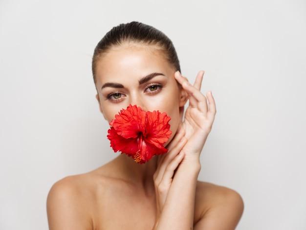 Vrouw met blote schouders rode bloem charme aantrekkelijke look