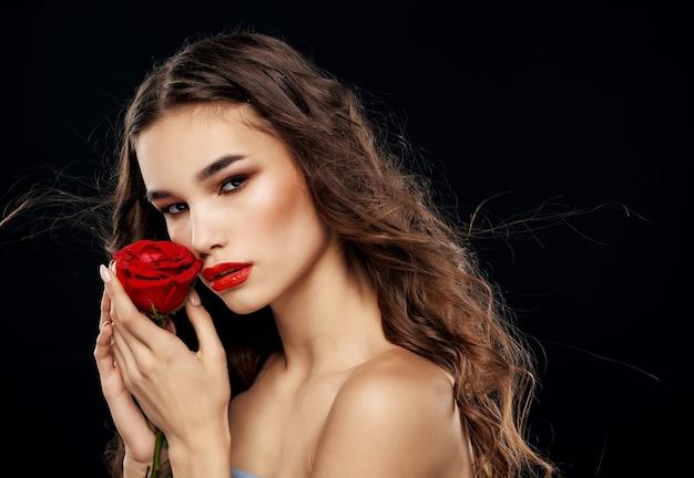 Vrouw met blote schouders rode roos in handen donkere achtergrond luxe