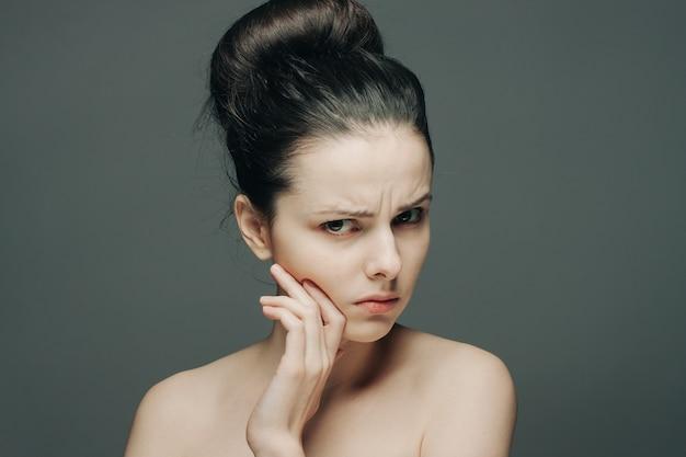 Vrouw met blote schouders verzameld haar ontevreden hand op gezicht