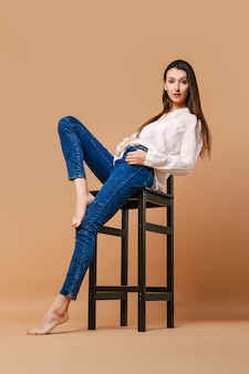 Vrouw met blote voeten en in casual outfit poseren op hoge houten kruk