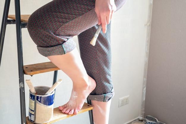Vrouw met blote voeten gekleurd met witte verf staat op trapladder met penseel in haar hand