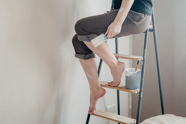 Vrouw met blote voeten gekleurd met witte verf zit bovenop op trapladder met penseel in haar hand