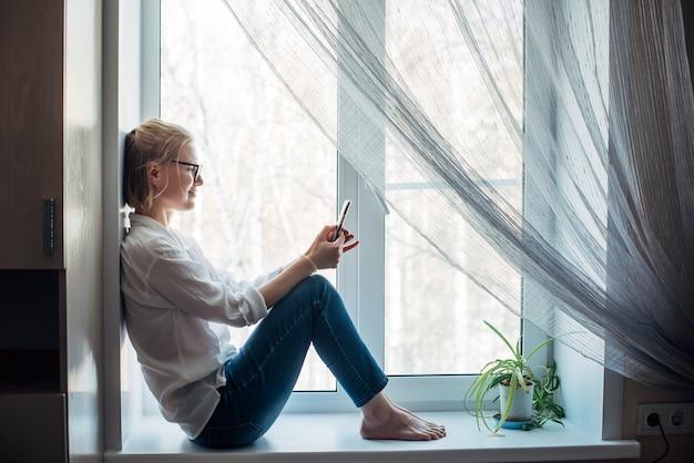 Vrouw met blote voeten in een bril, spijkerbroek zittend op de vensterbank in appartement, met smartphone