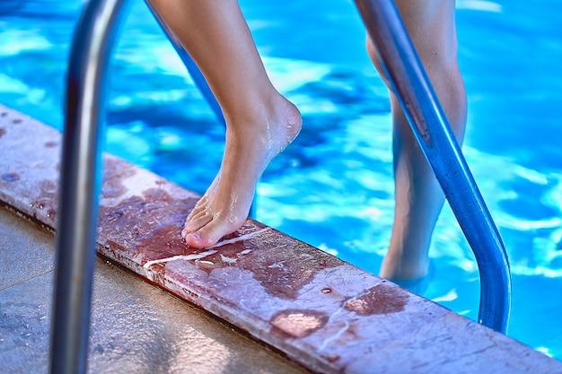 Vrouw met blote voeten met behulp van zwembad ladder in zwembad. preventie van nagelschimmel en huidinfecties in het zwembad, persoonlijke hygiëne