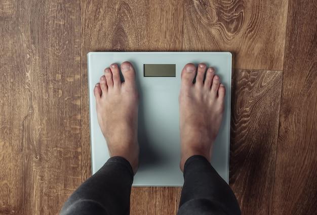 Vrouw met blote voeten wordt gewogen op de weegschaal op de vloer .. fitness concept