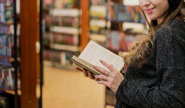 Vrouw met boek in de buurt van boekenplank