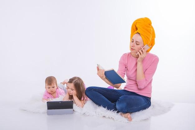 Vrouw met boek in haar handen praat over de telefoon. kinderen kijken cartoon op hun tablet. moeder waste haar haar. handdoek op het hoofd. hobby's en recreatie met gadgets.