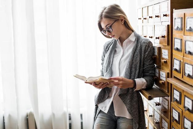 Vrouw met boek leunend op bibliotheekcatalogus