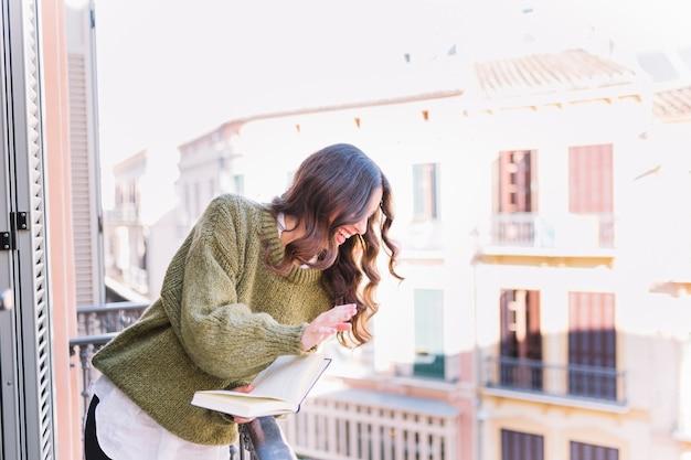 Vrouw met boek zwaaiende hand en lachen