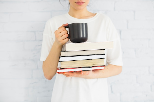 Vrouw met boeken en beker bijsnijden