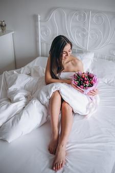 Vrouw met boeket bloemen in bed