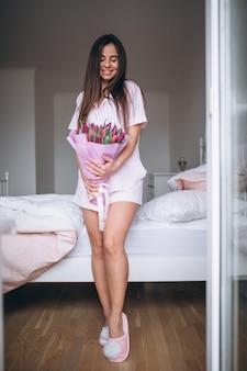 Vrouw met boeket bloemen in de slaapkamer