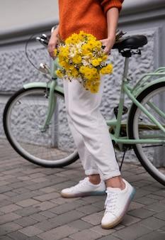 Vrouw met boeket bloemen met haar fiets buitenshuis
