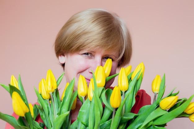 Vrouw met boeket gele tulpen mysterieus glimlachen, verjaardagscadeau