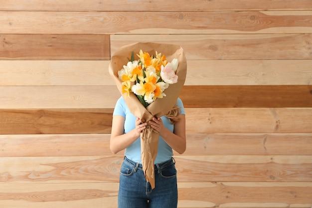 Vrouw met boeket van mooie bloemen op houten