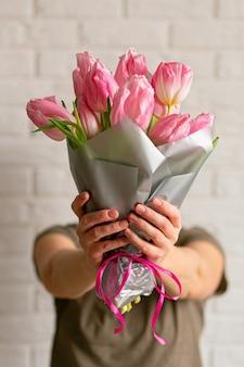 Vrouw met boeket van mooie roze lente tulpen in de buurt van witte bakstenen muur.