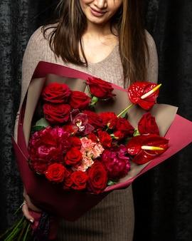Vrouw met boeket van roze en rode rozen anthurium en pioenrozen