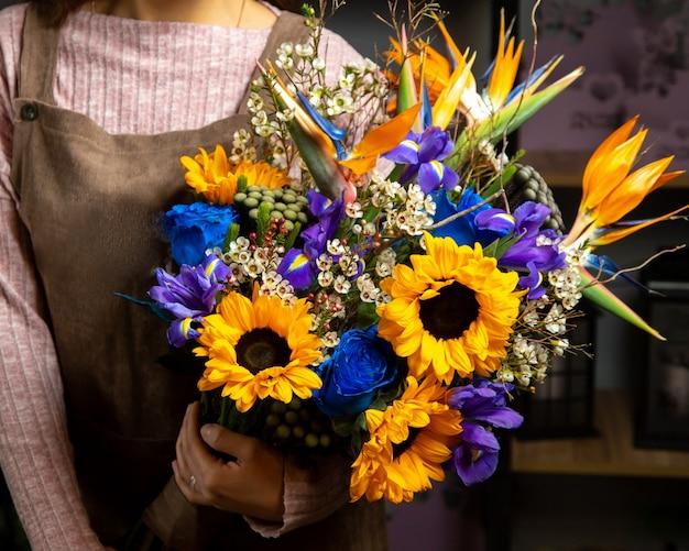 Vrouw met boeket van zonnebloemen iris en blauwe roos