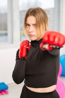 Vrouw met bokshandschoenen het uitoefenen