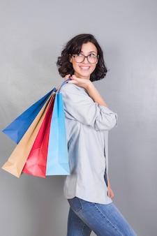 Vrouw met boodschappentassen achter rug