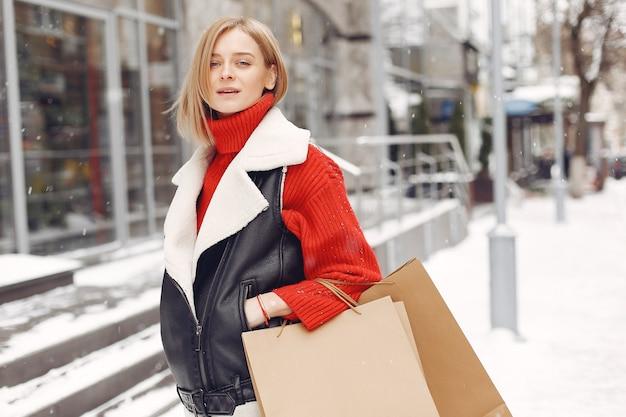 Vrouw met boodschappentassen bij een openluchtwinkelcomplex