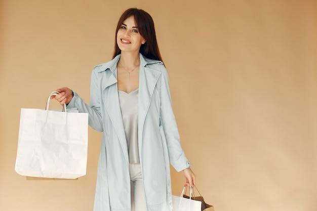 Vrouw met boodschappentassen. dame op een beige muur. vrouw in een blauwe jas.